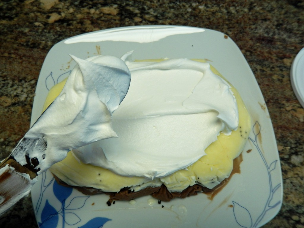 The ice cream layers get covered in whipped topping.